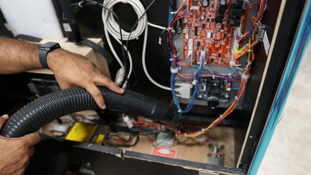 Vacuuming inside arcade cabinet.